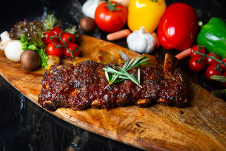 BBQ beef ribs steak served with a hot chili pepper and fresh tomatoes on an old vintage wooden cutting board Stock Photo