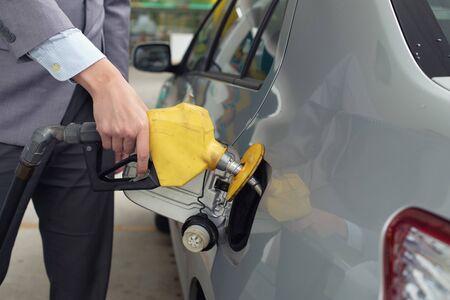 가스 펌프에서 가스를 펌핑합니다. 주유소에서 차에 휘발유 연료를 펌핑하는 남자의 근접 촬영. 미디엄