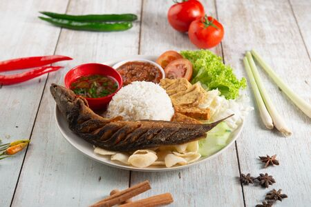 fried catfish with rice , sambal , vegables and mixed dish