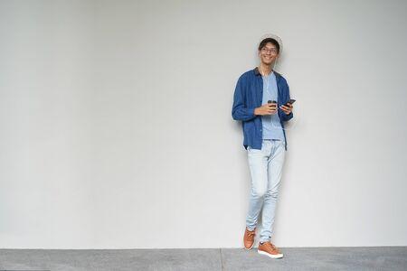 A asian teenage using phone with coffee