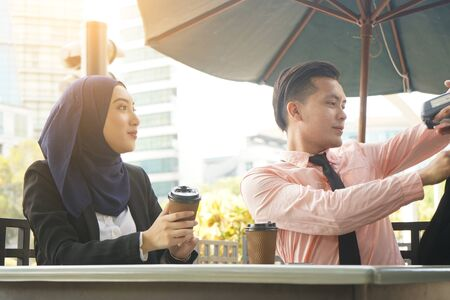 malay muslim business team using QR ewallet payment at cafe