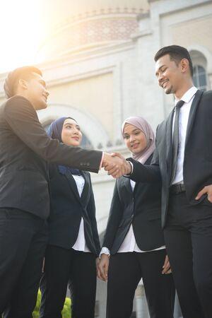 malay muslim business team handshaking during meeting