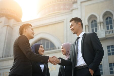 malay muslim business team handshaking during meeting
