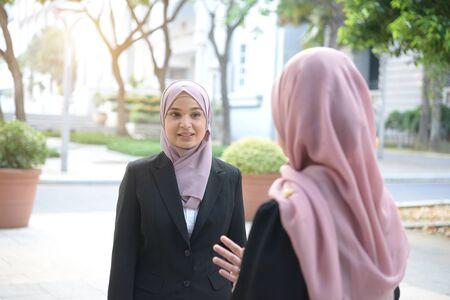 malay muslim business woman having conversation