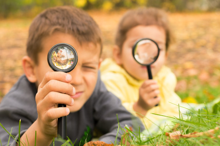 boy and girl look through a magnifying glass on the background of green grass and yellow leaves photo