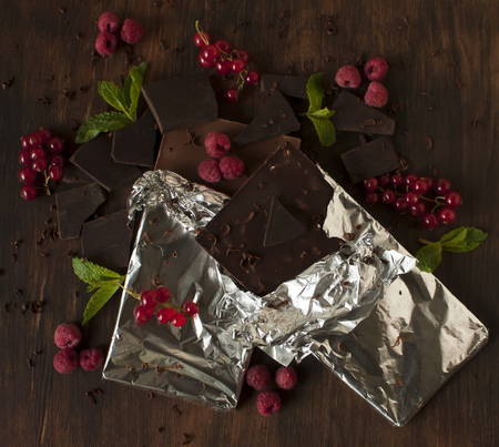 stuffing: Delicious still life with juicy berries of red currants, raspberries, mint leaves and tiled chocolate.