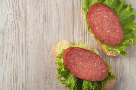 A sandwich with sausage and lettuce leaves. Standard-Bild - 103055640