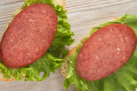 A sandwich with sausage and lettuce leaves. Standard-Bild - 103052807