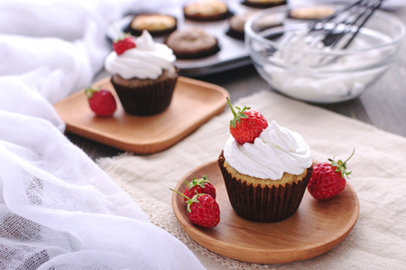 Tasty cupcakes with cream and berries on a wooden plate Reklamní fotografie