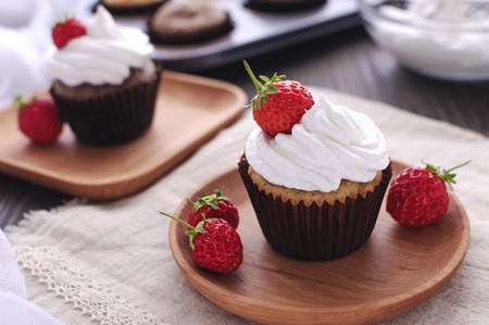 Tasty cupcakes with cream and berries on a wooden plate 免版税图像