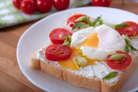 A delicious breakfast with poached egg, bread, cherry tomatoes, cheese and herbs. Poached egg for breakfast. Sandwich with cheese, red cherry tomatoes, herbs and poached egg. Foto de archivo