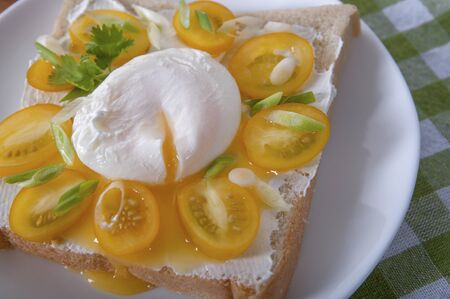 A delicious breakfast with poached egg, bread, yellow cherry tomatoes, cheese and herbs. Poached egg for breakfast. Sandwich with cheese, yellow cherry tomatoes, herbs and poached egg.