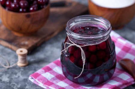Cherry jam for breakfast. Cooking jam in the summer season. Cooking, preserving berries. Foto de archivo