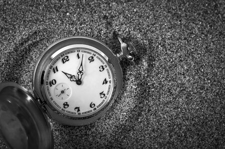 An old pocket watch lying in the sand. The clock fell in the sand. Time is running. Running time. Leaking time.
