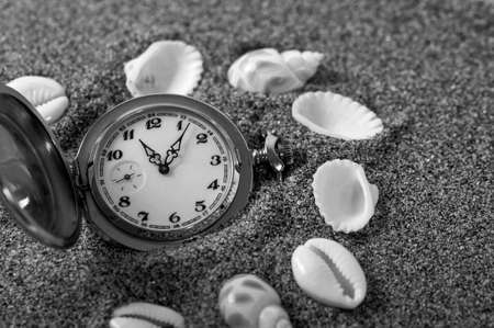 An old pocket watch lying in the sand surrounded by shells. The clock fell in the sand. Time is running. Running time. Leaking time.
