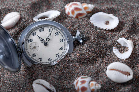 An old pocket watch lying in the sand surrounded by shells. Seashells. The clock fell in the sand. Time is running. Running time. Leaking time.