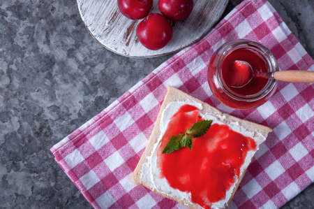 Breakfast from a sandwich with cheese and plum jam. Plum jam for breakfast. Tasty breakfast. Archivio Fotografico