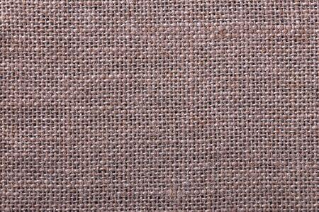 Weaving of twisted fiber, thread. Beautiful texture. Burlap fabric. Beautiful, braided fiber pattern. The rough burlap.