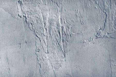 Old, gray wall with uneven putty applied. Interesting texture of the old wall. Uneven smears of putty on the wall. Foto de archivo
