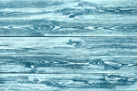 Background with unevenly applied paint, old and worn with a well-defined wood texture. Interesting texture of the wooden background. Background with a pronounced wood texture, colored green