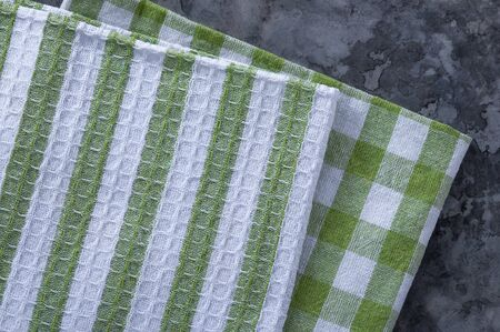A stack of towels and napkins lying on the table. Clean kitchen towels, hand wipes lying on the table. Order in the kitchen. Colored napkins, towels.