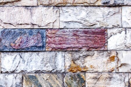 The wall is made of textured marble of different colors. A stone wall with an interesting marble texture. The marble facing of the wall.