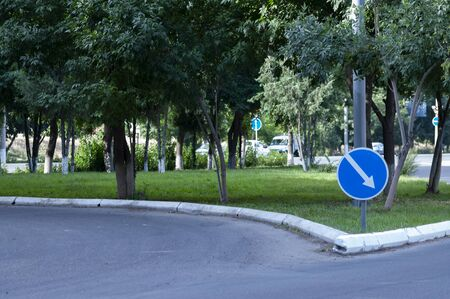 Street, blue round sign with a white arrow showing the turn. Round road sign with a white arrow.