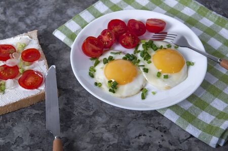 An appetizing breakfast with fried eggs, bread, cherry tomatoes and cheese. Fried eggs for breakfast. Sandwich with cheese and cherry tomatoes. Foto de archivo