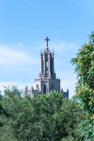 The Catholic Church in Tashkent in frame of greenery. Architectural building of the Church. Roman Catholic Temple of the Sacred Heart of Jesus. June 17, 2020, Uzbekistan, Tashkent city.