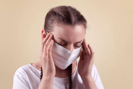 Girl in a medical mask. Girl on a yellow background. The girl is holding on to her temples, she looks tired, sickly. The girl is protecting herself from infection.