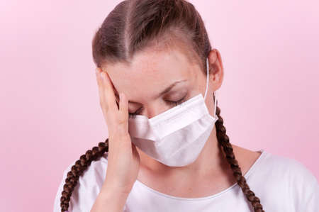 Girl in a medical mask. Girl on a pink background. The girl is protecting herself from infection. The girl is holding her head, she looks tired, sickly.