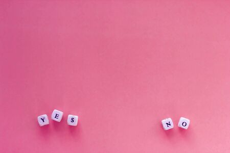 Yes or no choice on letter cubes. Choice, opinion, voting concept. Copyspace for text on trendy pink background.