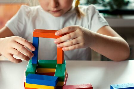 little blond girl playing board games. board games concept. wooden builing blocks in girl's hands. kids leisure project. Standard-Bild - 139601988
