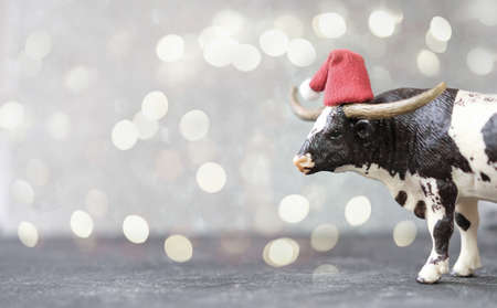 toy ox or bull in red santa hat as symbol of 2021 year. chinese calendar or horoscope. new year card or poster. bull on gray defocused background with bokeh. lights. happy new year concept.