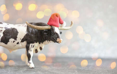 2021 year of the ox or bull. new year poster with toy bull in red hat defocused lights or bokeh. happy new year concept. selective focus.