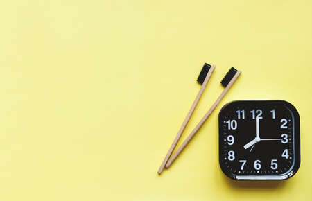 bamboo toothbrush with black bristles and Alarm clock on yellow background. Healthy teeth. Morning routine concept. top view shot.