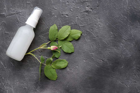 collagen peptides liquid. cosmetic product in a white glass flacon. collagen lotion in a spray bottle on gray background with rose hip bud. collagen lotion for anti age care and anti wrinkle beauty.