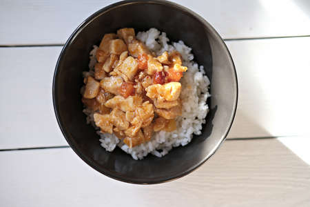Sweet and Sour Chicken with pineapple and bamboo served with steamed rice. caribbean style chicken. traditional delicious meal.