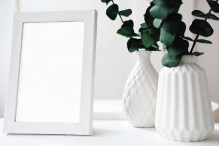 minimal style interior design of kitchen with mock up frame, eucaliptus leaves and white vases. Hipster Scandinavian Minimalistic interior. spring decor for modern look Banque d'images