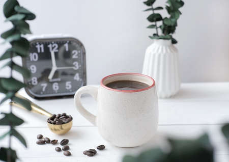 Breakfast relax time concept. coffee mug on a cozy kitchen table with alarm clock and green plants in vase. scandinavian minimal style. coffee beans in a spoon. time for yourself to start a good day.