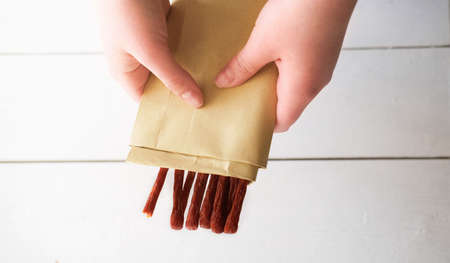 woman's hand holding biltong or jerked meat. traditional south african dried meat. biltong strips in craft pack. spicy food.