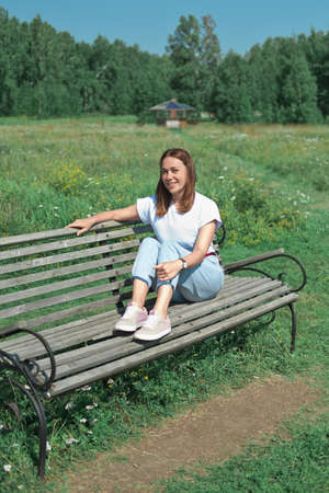 happy caucasian middle age woman sitting on a bench in a park. beautiful woman smiling and looking at camera.