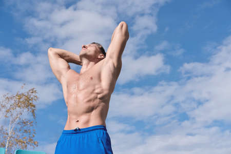 middle aged toned body man stands shirtless under sunlight and getting rest after workout. outdoors sport and active lifestyle. muscular caucasian man with toned abs relaxing on open air sportsground. 免版税图像