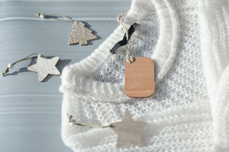 white knitted pullover with wooden tag mockup and wooden christmas tree. template for holiday sale or advertizing. wool sweater for cold season. Stock Photo