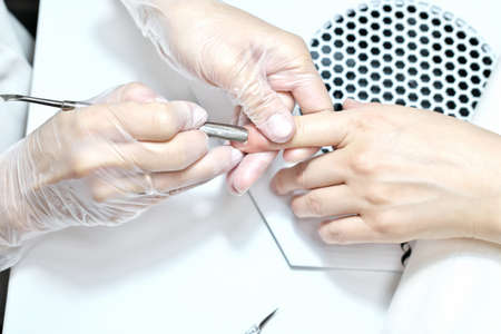 professional manicurist pushing cuticle on female hand with pushing tool. hand manicure process close up. salon and spa care for hands and nails.