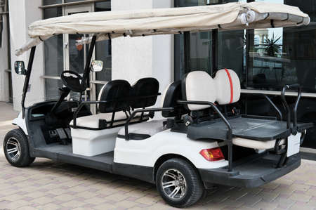 Electric buggy near hotel building. White golf cart with back seats waiting for passengers.
