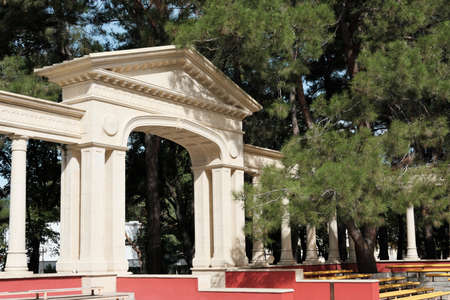 beautiful arch in ancient style in the forest park. a part of a scene for street show or presentations. columns or pillars and arch among coniferous trees.