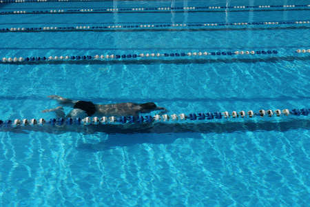 unrecognizable man of middle age swimming and diving in open air pool. back view of a man under water. sport and active lifestyle in middle age.