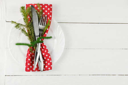 christmas decorated plate and tableware with red napkin and green ribbon. holiday silverware on white rustic table. festive christmas family dinner. Stock fotó