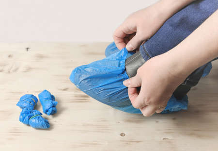 person's hands put on the blue shoe covers on boots in the hospital. shoe protective covers. hygiene in medical service office.